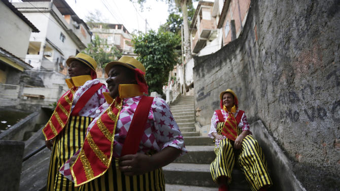 Anna Carvalho and her daughters Vania Regina and Cristina are dressed to participate in the carnival parade at the Sambadrome with the Sao Clemente samba school, in Rio de Janeiro