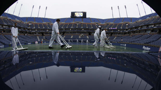 In this photo made with a fisheye lens, workers clear water from the court at Arthur Ashe Stadium during the U.S. Open tennis tournament in New York, Wednesday, Sept. 7, 2011. Because of rain, Wednesday's play at the U.S. Open will not start before noon. (AP Photo/Charlie Riedel)