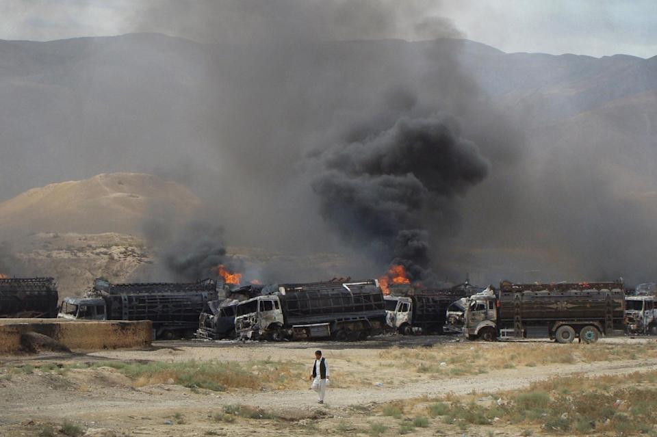 Black smoke risers from burning NATO supply trucks in Samangan, north of Kabul, Afghanistan, Wednesday, July 18, 2012. Afghan officials say a magnetic bomb placed on a truck exploded and destroyed 22 NATO supply vehicles in northern Afghanistan. (AP Photo/Javed Basharat)