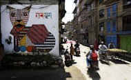 Nepalese travel past a mural in Kathmandu on August 20, 2013. Nepal's capital has been given a facelift thanks to a team of artists who have painted dozens of elaborate and metres-high murals on walls around the Himalayan city