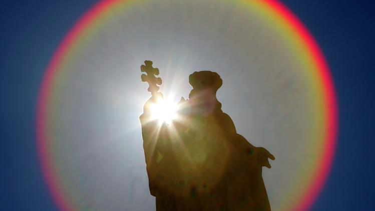 A halo from the sun appears around one of the statues in Saint Peter's Square at the Vatican