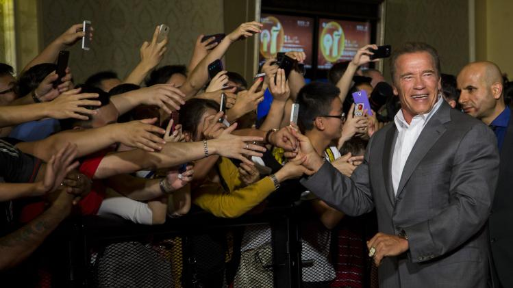 """Schwarzenegger shakes hand with fans as he arrives on the red carpet for the special screening of """"The Expendables 3"""" in Macau"""
