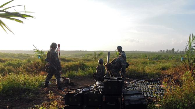 In this Tuesday, March 5, 2013 photo released by Malaysia's Ministry of Defense, Malaysian soldiers prepare to fire mortars toward the area where a stand-off with Filipino gunmen took place, at Tanduo village in Lahad Datu, Borneo's Sabah state, Malaysia. Malaysian security forces on Wednesday, March, 6, 2013 battled a group of Filipino intruders in the rugged terrain of Borneo after they escaped a military assault with fighter jets and mortar fire on their hideout, police said. One Filipino was shot and believed killed. (AP Photo/Malaysia's Ministry of Defense) EDITORIAL USE ONLY, NO SALES