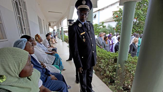 Secretary of State Hillary Rodham Clinton, far right, tours the Philippe Senghor Health Center in Dakar, Senegal, as female patients and security watch during her visit, Wednesday, Aug. 1, 2012. (AP Photo/Jacquelyn Martin, Pool)