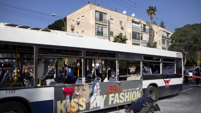 Israeli police officers examine a bus at the site of a bombing in Tel Aviv, Israel, Wednesday, Nov. 21, 2012. A bomb ripped through an Israeli bus near the nation's military headquarters in Tel Aviv on Wednesday, wounding several people, Israeli officials said. The blast came amid a weeklong Israeli offensive against Palestinian militants in Gaza. (AP Photo/Dan Balilty)