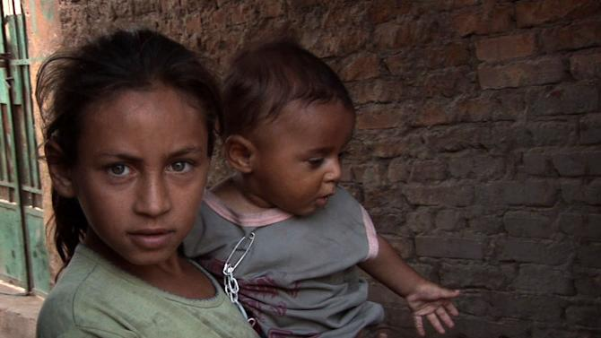 """In this publicity image released by Nat Geo Films, a sister and her baby brother who live in a cemetery in Cairo are shown in a scene from the documentary """"Life in a Day."""" (AP Photo/Nat Geo)"""
