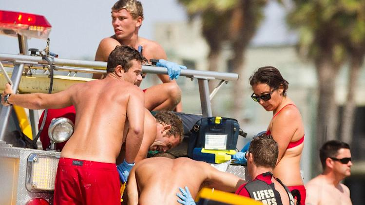Lifeguards assist a person who was in the water Sunday, July 27, 2014 in Los Angeles, after authorities said lightning struck 14 people, leaving two critically injured, as rare summer thunderstorms swept through Southern California. (AP Photo/Steve Christensen)