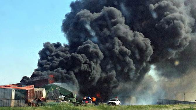 FILE - In this June 24, 2012, file photo, smoke rises from two cargo trains that collided near Goodwell, Okla. The National Transportation Safety Board meeting in Washington on Tuesday, June 18, 2013, is attempting to find a cause for the June 24, 2012, accident near Goodwell that killed three railroad workers.  (AP Photo/The Guymon Daily Herald, Trudy Hart, File)