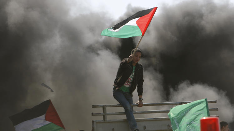 "Demonstrators wave a Palestinian flag during a rally marking ""Land Day"" in Beit Hanoun, northern Gaza Strip, Friday, March 30, 2012. The ""Land Day"" rallies are an annual event marked by Israeli Arabs and Palestinians in the West Bank and Gaza who protest what they say are discriminatory Israeli land policies.(AP Photo/Adel Hana)"
