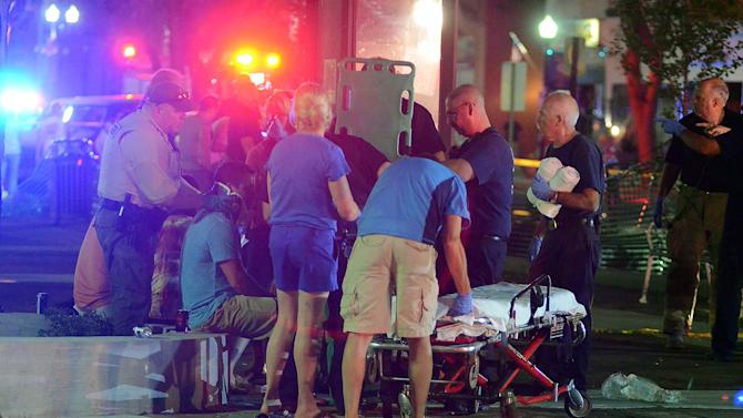 Emergency workers treat injured bystanders after a motorist drove into the Rally n Lima's Town Square on Friday, June 15, 2012 in Lima, Ohio. A 63-year-old woman drove her car into the crowded town square and struck bystanders, sending some through the air and injuring about 30 people, some of whom were pinned under the car and freed when bystanders lifted it, authorities and witnesses said. No one was killed, but some victims suffered serious injuries to their legs, heads and necks, police said.   (AP Photo/The Lima News, Craig J. Orosz) MANDATORY CREDIT