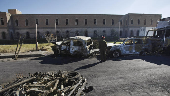 A Yemeni soldier looks at damaged vehicles at the scene where a suicide car bomber and heavily armed gunmen, killed scores and wounded more than a hundred in a fierce battle in the heart of Yemen's capital of Sanaa last Thursday, Dec. 5, 2013, at the Defense Ministry complex in Sanaa, Yemen, Monday, Dec. 9, 2013. Among the dead at the Defense Ministry complex, which also houses a military hospital, were soldiers and civilians, including seven foreigners — two Germans, two Vietnamese, two Filipinos and one Indian, according to the Supreme Security Commission. (AP Photo/Hani Mohammed)