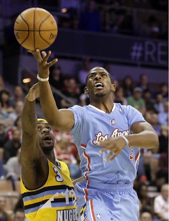 The Los Angeles Clippers' Chris Paul, right, shoots over the Denver Nuggets' Ty Lawson during the first half of a preseason NBA basketball game on Saturday, Oct. 19, 2013, in Las Vegas. The Clippers d