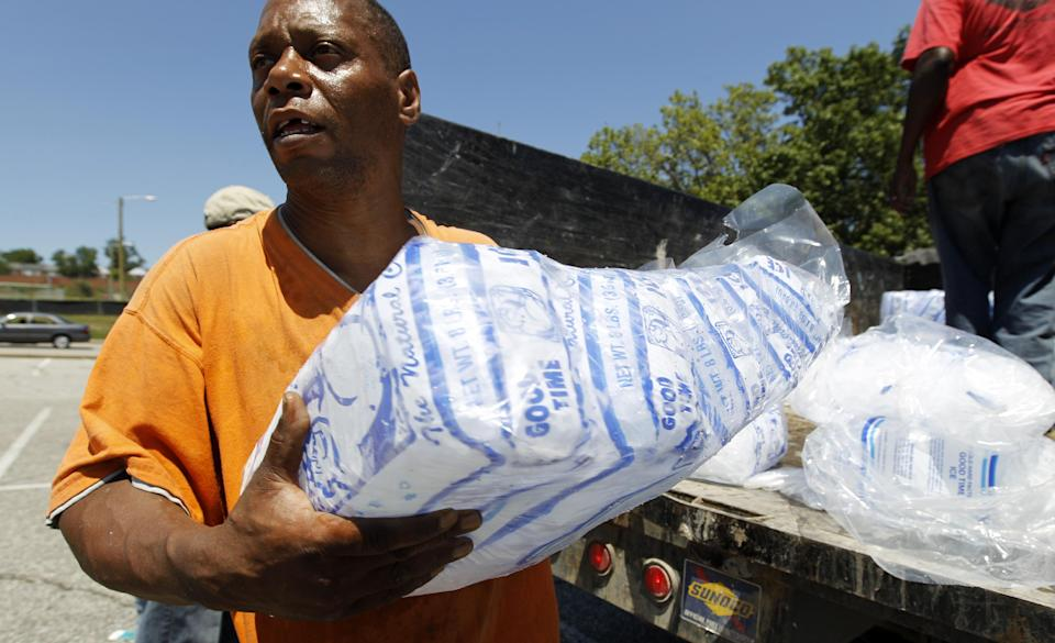 Baltimore city worker Joe Lane gives away free bags of ice to residents at the Northwood Plaza shopping center in Baltimore on Monday, July 2, 2012.  Around 2 million customers from North Carolina to New Jersey and as far west as Illinois were without power Monday morning after a round of summer storms.  (AP Photo/Jose Luis Magana)