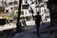 A Syrian rebel walks in a heavily damaged street in the Salaheddin district of the northern city of Aleppo on September 6