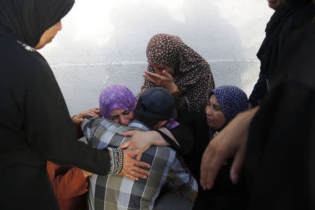 Palestinians mourn outside a morgue in Gaza City
