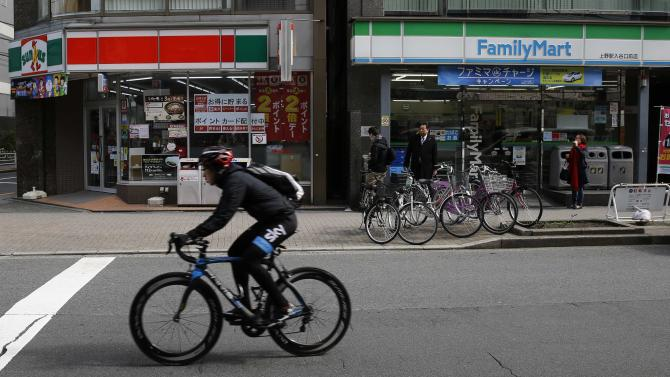 A man rides on a bike in front of a FamilyMart and UNY Group Holdings Co's Sunkus convenience stores in Tokyo