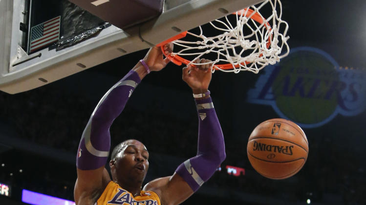 Los Angeles Lakers' Dwight Howard, top, dunks as Dallas Mavericks' Brandan Wright, right, and Shawn Marion watch in the first half of an NBA basketball game in Los Angeles, Tuesday, Oct. 30, 2012. (AP Photo/Jae C. Hong)