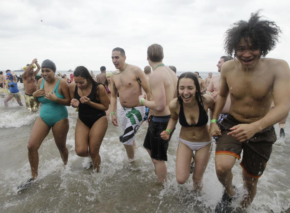 A group of swimmers exit the water after taking the plunge in 30-degree temperatures during the 110th annual Coney Island Polar Bear Club ocean swim at Coney Island in New York, Tuesday, Jan. 1, 2013.  (AP Photo/Kathy Willens)