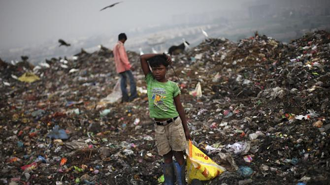 In this Sept. 13, 2012 photograph, a young Indian ragpicker pauses for a while as he goes about the routine of searching through garbage for reusable garbage at a dumping ground on the outskirts of New Delhi, India. Those whose survival depends on this gray market in trash fear their lives are about to be upended. Because where they see money in those mountains of garbage, the New Delhi government sees electricity. Desperate for cheap energy, the Delhi government is experimenting with power plants fueled by garbage. One plant is now running on a trial basis and two more are under construction. (AP Photo/Altaf Qadri)
