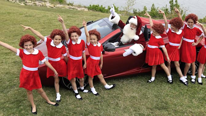 With several Annies on hand, Brady White portrays Santa Clause, center, as they pose with a 2013 McLaren 12C spider sports car during the unveiling of the Neiman Marcus 2012 Christmas Book in Dallas, Tuesday, Oct. 9, 2012. Shoppers can shell out $30,000 buying a walk on role in the Broadway musical Annie and $354,000 gets the car. (AP Photo/LM Otero)