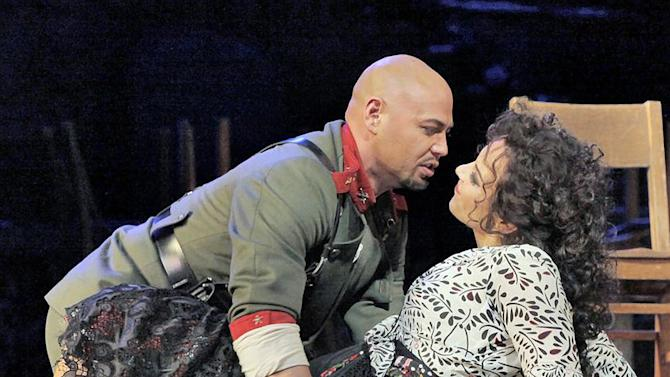 "In this undated photo provided by the Metropolitan Opera, Keith Miller, left, plays Zuniga in Bizet's ""Carmen"" with Elina Garanca in the title role at the Metropolitan Opera in New York. Miller, a former University of Colorado fullback, has reinvented himself, going from the gridiron to the stage and will appear in Verdi's ""Un Ballo in Maschera,"" at the Metropolitan Opera. Performances begin Thursday, Nov. 8, 2012. (AP Photo/Metropolitan Opera, Ken Howard)"