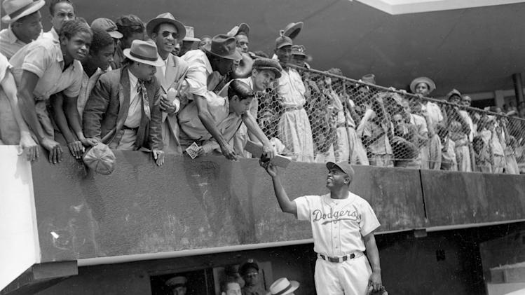 FILE - In this March 6, 1948, file photo, Jackie Robinson, first baseman of the Brooklyn Dodgers, returns an autograph book to a fan in the stands, during the Dodgers' spring training in Ciudad Trujillo, now Santo Domingo, in the Dominican Republic. Baseball holds tributes across the country on Jackie Robinson Day, Tuesday, April 15, 2014, the 67th anniversary marking the end of the game's racial barrier. (AP Photo/File)
