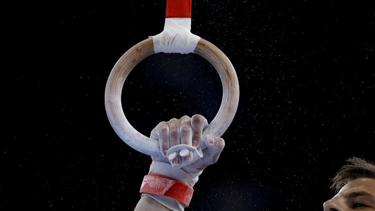 The hand of Panagiotis Aristotelous grips on as he performs on the rings during the Men's All-Around gymnastics competition at the Scottish Exhibition Conference Centre during the Commonwealth Games 2014 in Glasgow, Scotland, Wednesday July 30, 2014. (AP Photo/Kirsty Wigglesworth)