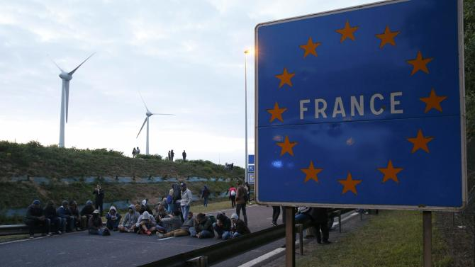 """Migrants sit to block the road near a sign marked """"France"""" in Coquelles, near Calais"""
