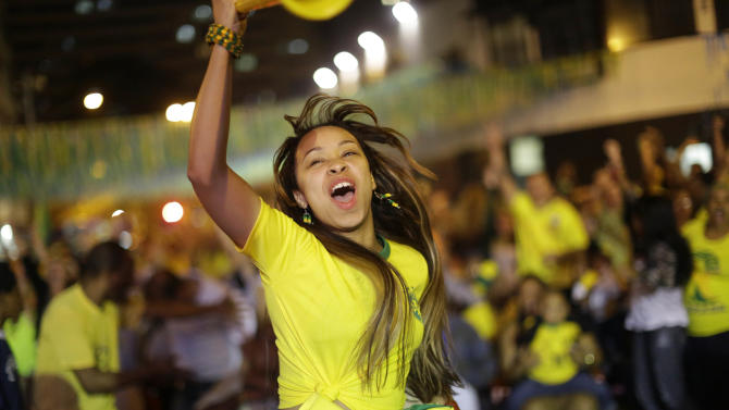 A Brazilian soccer fan celebrates after Brazil scored against Cameroon, while watching the match on a giant television screen in Bixiga neighborhood in Sao Paulo, Brazil, Monday, June 23, 2014. Brazil's Neymar scored twice in the first half to lead Brazil to a 4-1 win over Cameroon on Monday, helping the hosts secure a spot in the second round of the soccer World Cup. (AP Photo/Nelson Antoine)