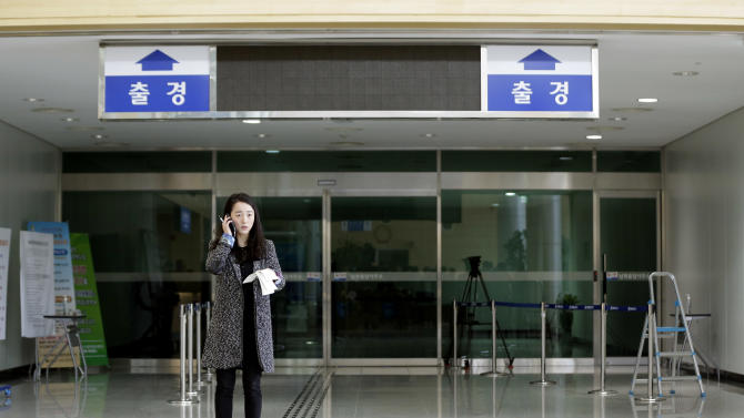 "A reporter uses her mobile phone in front of a closed immigration gate for the North Korean city of Kaesong at the customs, immigration and quarantine office near the border village of Panmunjom, which has separated the two Koreas since the Korean War, in Paju, north of Seoul, South Korea, Monday, April 8, 2013. North Korea raised tensions Wednesday when it barred South Koreans and supply trucks from entering the Kaesong industrial complex, where South Korean companies have employed thousands of North Korean workers for the past decade. The writing reads ""Departure."" (AP Photo/Lee Jin-man)"