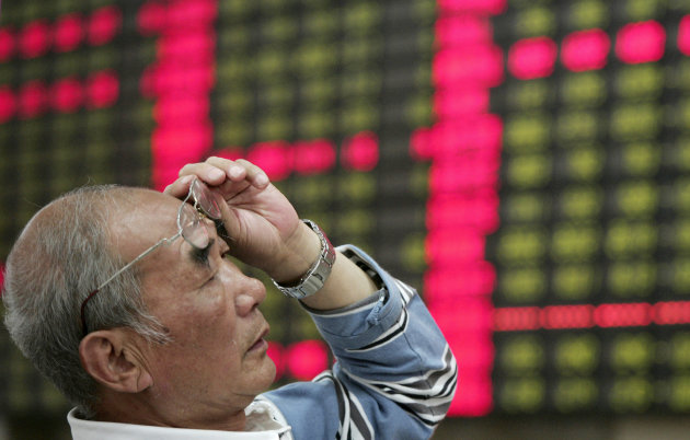 An investor looks at the stock price monitor at a private securities company Monday June 4, 2012 in Shanghai, China. Chinese shares lost ground Monday, with the benchmark Shanghai Composite Index fall