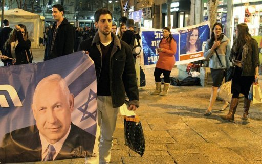 <p>A supporter of the Likud party holds a banner showing Israeli Prime Minister and party leader Benjamin Netanyahu, on January 21, 2013 at the Ben Yehuda Mall in Jerusalem. Israelis vote Tuesday in a general election expected to return Netanyahu to power at the head of a government of hardline right-wing and religious parties.</p>