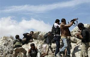 Free Syrian Army fighters fire their weapons during what they said were clashes with forces loyal to Syria's President al-Assad at Al-Arbaeen mountain in Idlib countryside