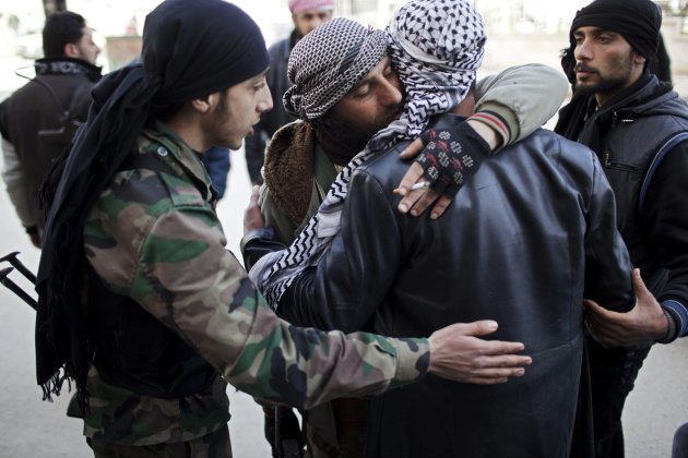 Free Syrian Army fighters console a comrade after an ambulance carried an injured friend to a hospital during fierce fighting against government troops in Idlib, north Syria, Saturday, March 10, 2012.