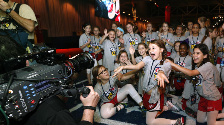 New Orleans kids cheer for a television camera at the Quaker's NFL Experience in New Orleans on Wednesday, Jan. 30, 2013. (Jonathan Bachman / AP Images for Quaker Oats)