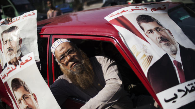 A supporter of Egypt's ousted President Mohammed Morsi holds a banner with Morsi's image, during a march against Egyptian Defense Minister Gen. Abdel-Fattah el-Sissi in Nasr City, Cairo, Egypt, Friday, Aug. 2, 2013. (AP Photo/Manu Brabo)