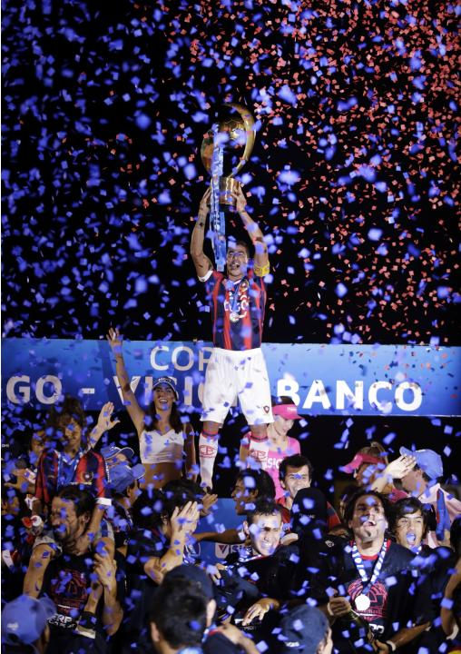Cerro Porteno's Bonet celebrates with the trophy after defeating Nacional during their Paraguay Primera Division match to win the championship in Asuncion
