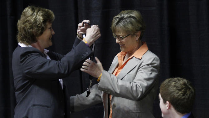"Former Tennessee women's college basketball coach Pat Summitt, left, give her whistle to new head coach Holly Warlick, center, as her son,  Tyler Summitt, right watches during a news conference Thursday, April 19, 2012, in Knoxville, Tenn. Summitt said it's been a ""great ride"" and it is the right time for her to step down after coaching the Tennessee Lady Vols for nearly four decades. (AP Photo/Wade Payne)"