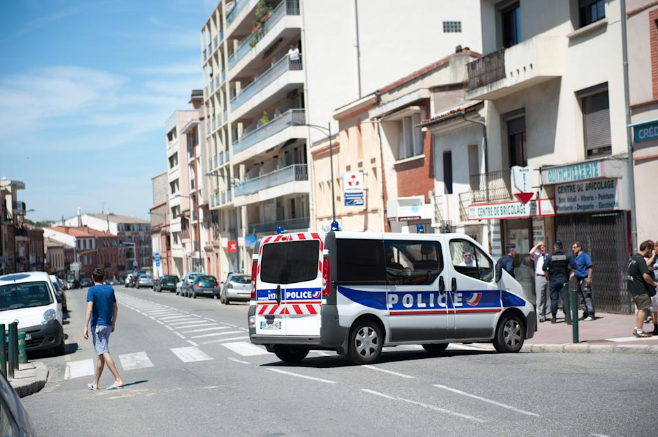 Police officers secure a street near where a man took hostages in a bank in the southern French city of Toulouse and fired a shot, police said, Wednesday, June 20, 2012. French television reported that he claimed allegiance to the al-Qaida terrorist group.(AP Photo/Bruno Martin)