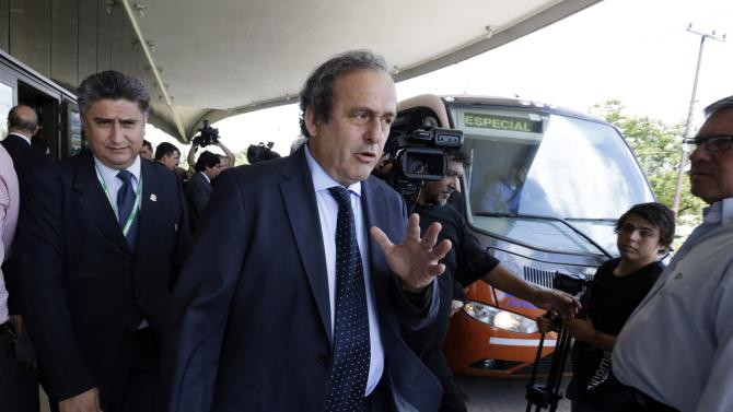 UEFA President Michel Platini gestures as he leaves a hotel in Luque