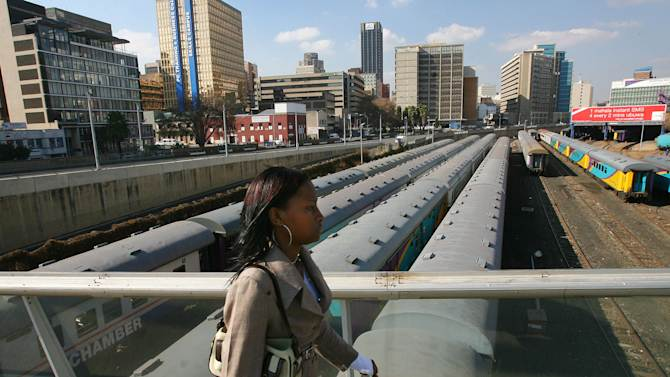 File: In this photo taken Thursday June 29, 2006 a Johannesburg resident walks on Mandela Bridge above trains over the railroad tracks in Johannesburg.  South Africa has accepted a Canadian dlrs 5.8 billion (euro 4.5 billion) deal with French company Alstom SA to refurbish the nation's passenger trains. The deal is one of the largest ever signed by the government since the end of apartheid, the Passenger Rail Agency of South Africa  announced the deal Wednesday Dec. 5, 2012. (AP Photo/Jerome Delay-file)