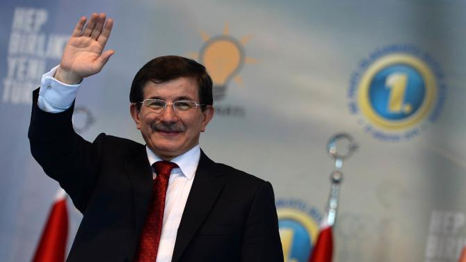 Turkish Foreign Minister and ruling Justice and Development Party (AKP) chairman candidate Ahmet Davutoglu greets his supporters on August 27, 2014