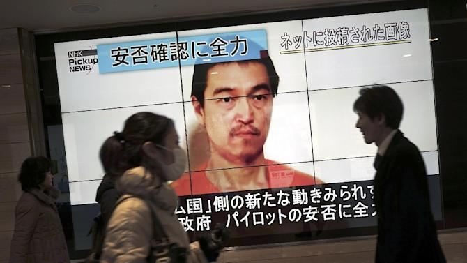People walk by a screen showing TV news reports of Japanese hostage Kenji Goto, held by the Islamic State group, in Tokyo Saturday, Jan. 31, 2015.  The fates of the Japanese journalist and a Jordanian military pilot were still unknown Saturday after the latest purported deadline for a possible prisoner swap lapsed with no further messages from the Islamic State group holding them captive. (AP Photo/Eugene Hoshiko)