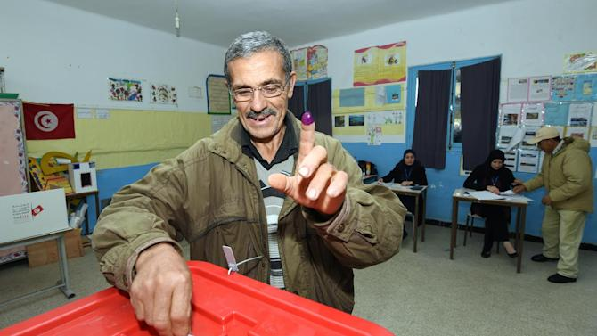 A Tunisian man raises his ink-stained finger as he casts his vote on December 21, 2014 at a polling station in Tunis
