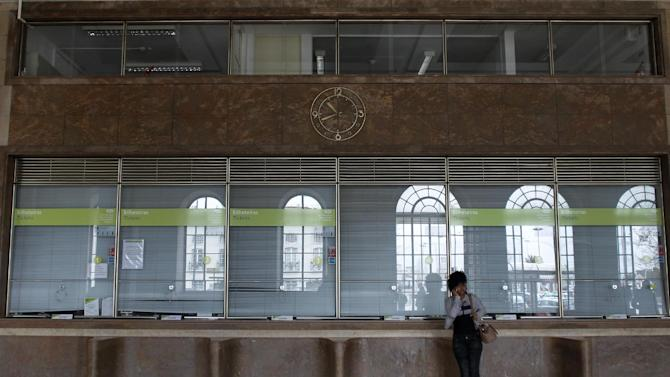 A woman talks on the phone as stands next to closed tickets counters at Lisbon's Santa Apolonia train station during a 24-hours strike by Portuguese railway workers, Wednesday, March 6, 2013. The strike was a part of a week of disruptions and protests throughout the country by general transport workers, that included trains, buses, subway and boats. (AP Photo/Francisco Seco)