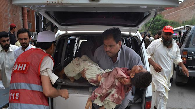 A Pakistani carries a critically injured boy, a victim of a car bombing, from an ambulance upon his arrival at a local hospital in Peshawar, Pakistan, Sunday, June 2013. A car bomb exploded as a convoy of paramilitary troops passed through the outskirts of the northwest Pakistani city of Peshawar, killing at least a dozen people and wounding scores of others, police said. (AP Photo/Hussain Ali)