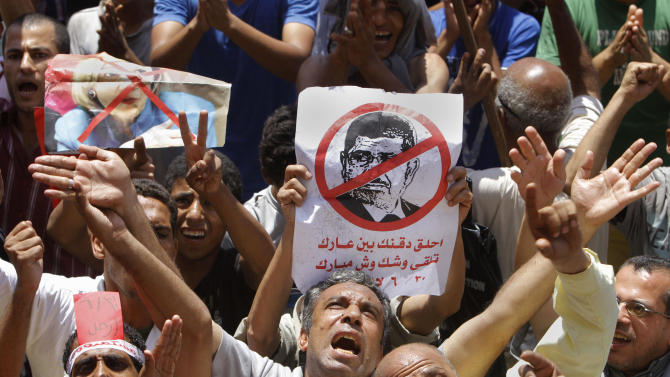 """Egyptian protesters shout anti-Muslim Brotherhood slogans as they hold posters depicting U.S. Ambassador to Egypt Anne Patterson and President Mohammed Morsi during a protest in Tahrir Square, the focal point of Egyptian uprising, in Cairo, Egypt, Friday, June 28, 2013. Arabic on the poster at center reads, """"shave your beard show your shame, you will look like Mubarak."""" Egypt's opposition plans to bring out massive crowds on Sunday in protests nationwide, vowing to force President Mohammed Morsi to step down. Across the city from a pro-Morsi rally Friday, thousands massed in Cairo's central Tahrir Square, shouting for the president to """"leave, leave,""""(AP Photo/Amr Nabil)"""