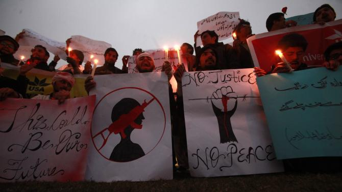 People hold candles and signs to condemn the Taliban attack on the Army Public School in Peshawar, during a rally in Lahore