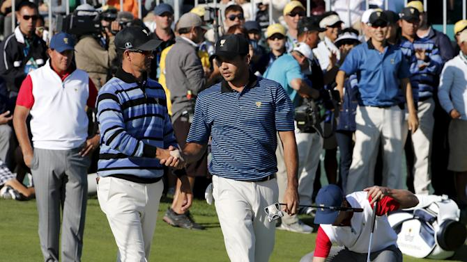 International team members Day and Scott of Australia shake hands after Day sank his putt on the 18th hole as U.S. team member Mickelson and Johnson in the background during the four ball matches of the 2015 Presidents Cup golf tournament at the Jack Nick