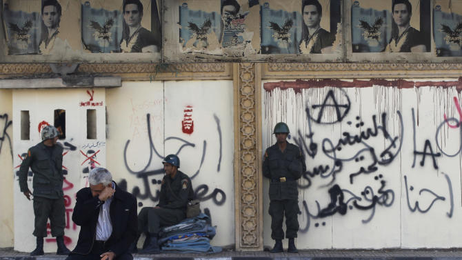 "A man sits on a bench as soldiers guard the presidential palace in Cairo, Egypt, Thursday, Dec. 13, 2012. Egypt's opposition called on its followers to vote ""no"" in a crucial referendum on a disputed constitution drafted by Islamist supporters of President Mohammed Morsi. (AP Photo/Petr David Josek)"